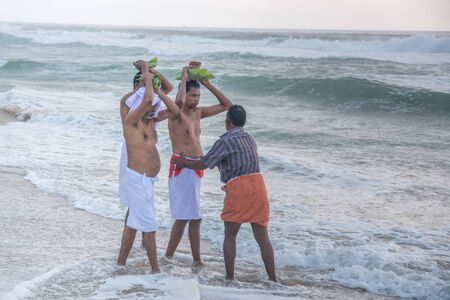 personas tomando agua: Varkala, India - December 11, 2016 - People and pilgrims praying at holy beach Varkala in Kerala, South India and taking a bath in the holy water