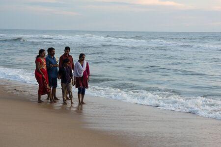 personas tomando agua: Varkala, India - 11 diciembre 2016 - Las personas y peregrinos rezando en santa Varkala playa en Kerala, sur de la India y de tomar un baño en el agua bendita