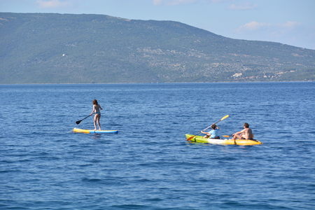 Cres, Croatia - June 18, 2017 - Girl on stand up paddleboard