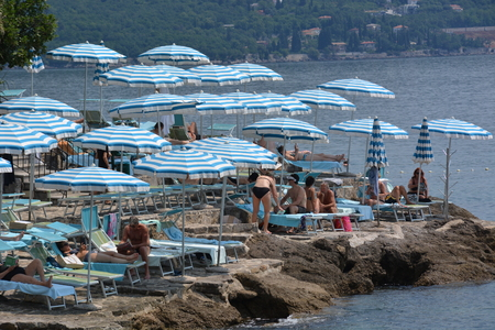 croatian: Opatija, Croatia - June 13, 2017 - Sunbathing and swimming by Lungomare promenade near Opatija