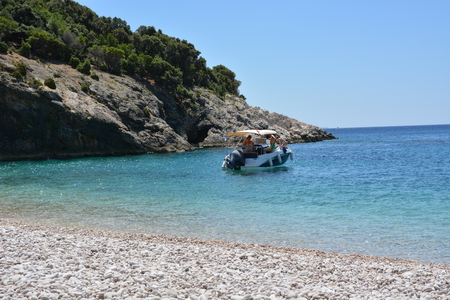 Lubenice, Croatia - June 19, 2017 - Beach of blue grotte near Lubenice with boats and blue sky