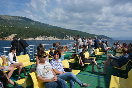 Cres, Croatia - June 16, 2017 - Car ferry on its way to island Cres with passengers in the sun