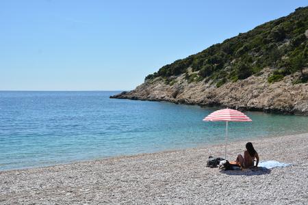 Lubenice, Croatia - June 19, 2017 - Beach of blue grotte near Lubenice with boats and blue sky
