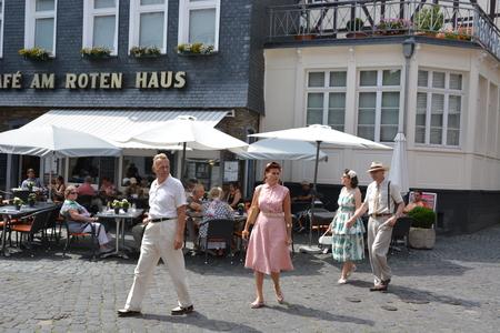 postwar: Monschau, Germany - July 22, 2017: People in old-fashioned clothing walking through Monschau