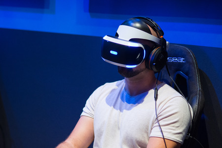 Cologne, Germany - August 26, 2017 - Young people playing flight simulator with virtual reality eyeglasses