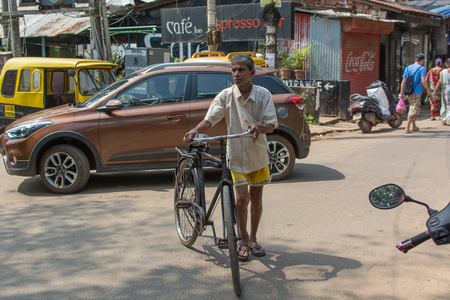 Goa, India - July 8, 2018 - Cyclist in typical traffic situation on indian street in Canacona - Goa Reklamní fotografie - 116967825