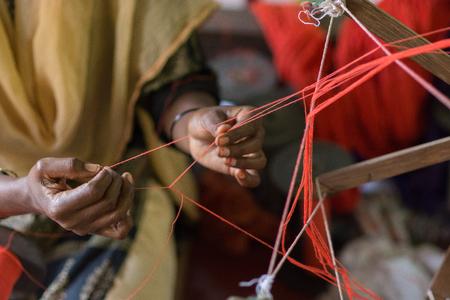 Mumbai, India - July 8, 2018 - Indian craftwoman weaving a carpet Editorial
