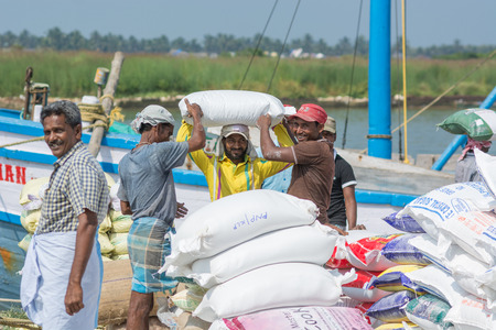 Mumbai, India - July 8, 2018 - Indian workers unloading bags with sand from ship in harbor for a construction site