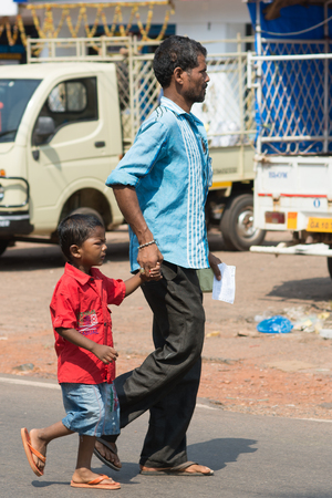 Goa, India - July 8, 2018 - Man with his boy on indian street in Canacona - Goa Editorial