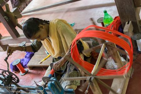 Mumbai, India - July 8, 2018 - Indian craftwoman weaving a carpet