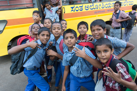 Mumbai, India - July 8, 2018 - Children from childrens home waiting for yellow school bus paid by an international charity project
