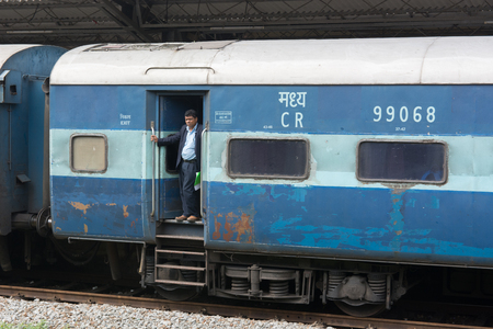 Mangalore, India - July 8, 2018 - Man waiting for train to depart in slow indian traffic system Editorial