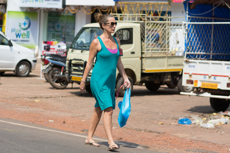 Goa, India - July 8, 2018 - European pedestrians in typical traffic situation on indian street in Canacona - Goa