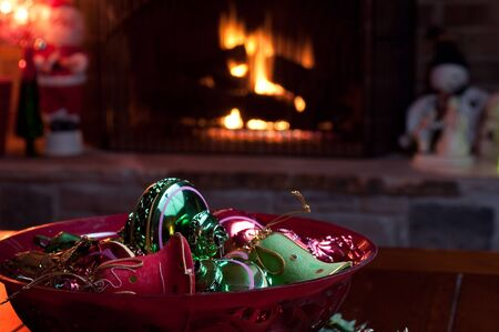 fireplace: Antique red and green Christmas ornaments shaped like bells and other shapes, in a red bowl, in front of a fireplace. Santa Claus and Snowman dolls in the background. Stock Photo