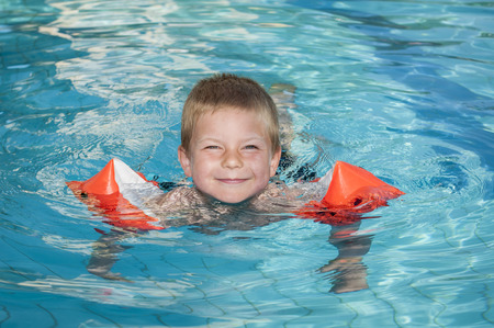 teh: Smiling boy enjoying the swimming pool with teh safety of inflatable arm bands  Stock Photo