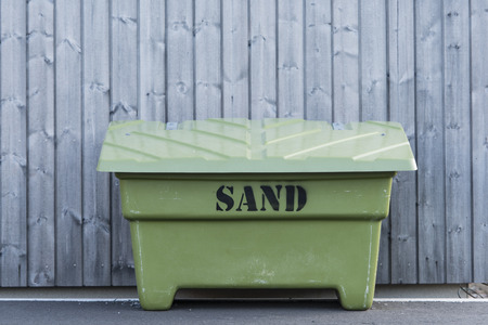 gritting: Green grit box with sand to prevent accidents on icy pavement