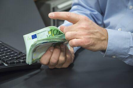 the clerk: Primer plano de empleado de banco contando billetes de 100 euros