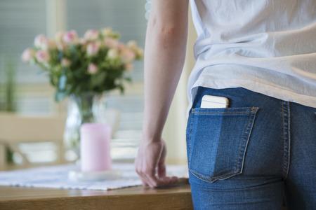 in jeans: Primer plano de una ni�a en la camiseta blanca y pantalones vaqueros azules con una c�lula o un tel�fono m�vil en su bolsillo trasero.