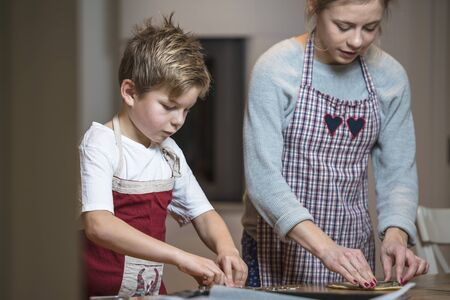bisquit: Kids baking gingerbread at home for christmas.