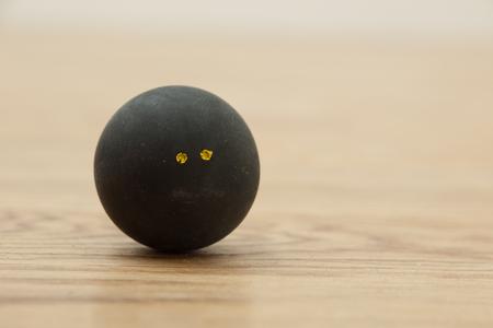 racquetball: Doble punto amarillo oficial pelota de squash negro en el parquet en pista de squash Foto de archivo