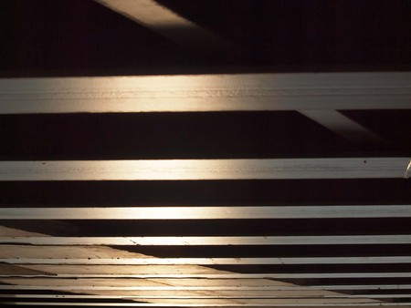 solidity: Bottom view of a wooden bridge, illuminated by sun-rays of the sunset