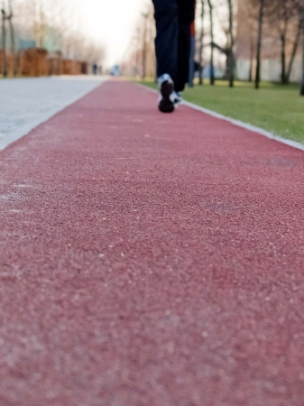 A person is jogging in blue tracksuits and trainers on a red, rubber covered running track photo