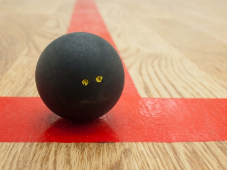 squash: Double yellow dot official black squash ball on the red t-line in squash court