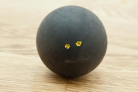 racquetball: Doble punto amarillo oficial pelota de squash negro en el parquet en una pista de squash Foto de archivo