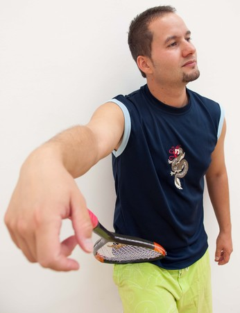 racquetball: Un jugador de squash se apoya una raqueta de squash en frente de la pared lateral de una pista de squash Foto de archivo