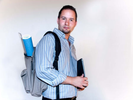 self exam: A young man is standing with a backpack with a ruler and a plan holder in it and is holding a folder in his hand in gray shirt