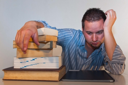 surfeit: A young man is sitting by a desk with several books in gray shirt
