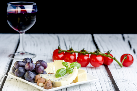 tabla de quesos: Appetizers - small plate of blue cheese, camembert cheese, grapes and walnuts Foto de archivo