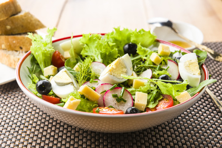 Light meal - salad with rucola, tomato, egg and olives Stock Photo