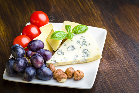Appetizers - small plate of blue cheese, camembert cheese, grapes and walnuts Stock Photo