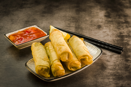 Spring rolls with vegetables, chopsticks and sweet and sour sauce
