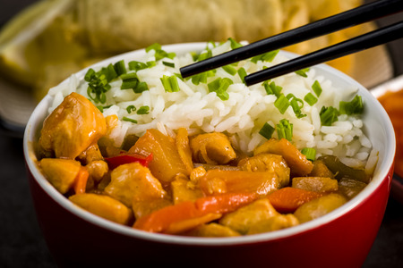 Chicken in sweet and sour sauce with rice and spring rolls
