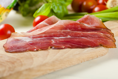 A few slices of Parma ham on a wooden board
