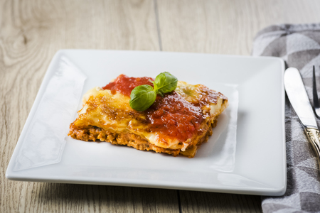 an appetizing portion of lasagna on a white plate topped with tomato sauce
