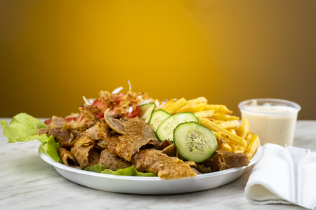 meat with kebab, French fries and salad on a plastic plate Stockfoto