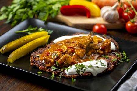 Kartoffelpastete serviert mit Schweineeintopf mit Champignons
