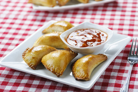 Empanada - a dish of South American cuisine - baked dumplings stuffed with meat and vegetable