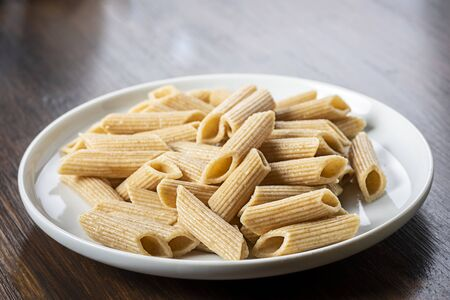 pasta, wholemeal penne - stock photo