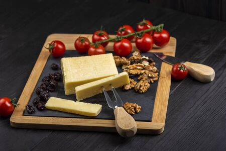 cheese board - cheddar cheese with nuts, cranberries and cherry tomatoes Reklamní fotografie
