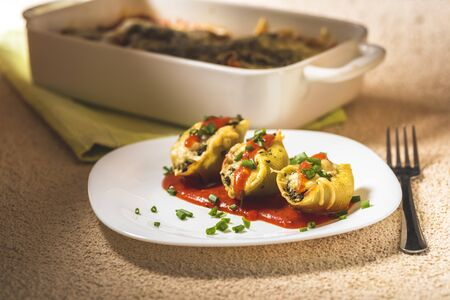shell-shaped pasta stuffed with spinach and cheese baked in tomato sauce