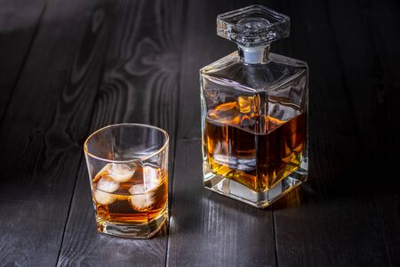 carafe and glass with whiskey on a wooden black table