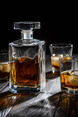 a glass of whiskey with ice on a wooden black table Stock Photo