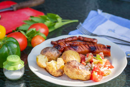 grilled sausage with baked potatoes and tomato salad Stok Fotoğraf