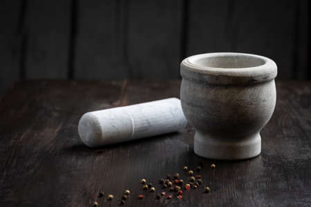 kitchen mortar on a wooden table and scattered grains of colored pepper