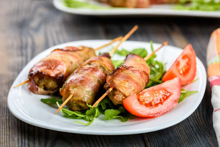 Kofta kebab - skewers of minced meat surrounded by slices of bacon