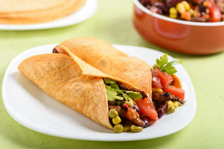 Tacos - delicious tortillas with meat and vegetables served with a spicy sauce Stock fotó